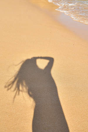 shadow from the photographer girl in the sand, silhouette in the sand, wave Stock fotó