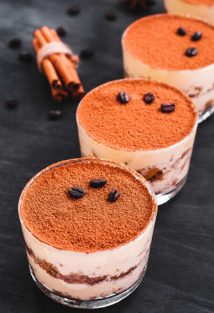 gourmet tiramisu dessert in a glass sprinkled with cocoa and decorated with coffee beans on a dark background Stock fotó