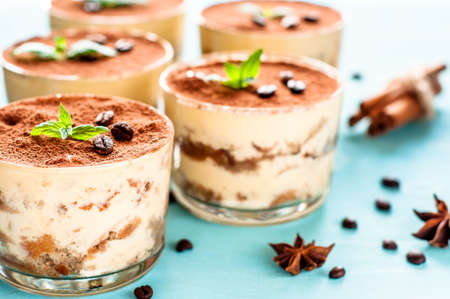 tiramisu in a glass decorated with coffee beans on dark background