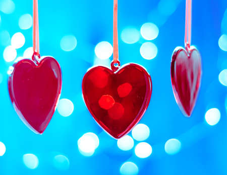 Hanging crimson Christmas Heart toy on on a glowing colorful background Stock fotó