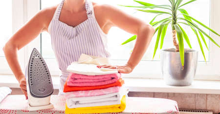 Happy young beautiful woman ironing clothes. Housework