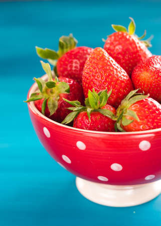 bright print bowl of fresh strawberries on blue wooden background