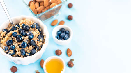 healthy breakfast: oatmeal with blueberries and nuts in a white bowl