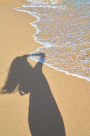 shadow from the photographer girl in the sand, silhouette in the sand, wave Reklamní fotografie