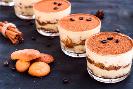gourmet tiramisu dessert in a glass sprinkled with cocoa and decorated with coffee beans on a dark background Reklamní fotografie