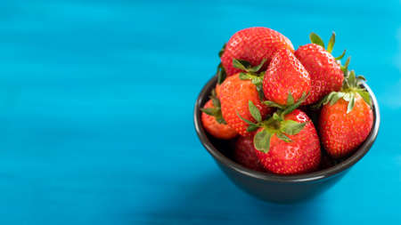 blue cloth with a bowl of fresh strawberries on a wooden table