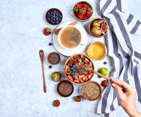 Top view showing hands eating porridge with honey nuts, blueberries on white wooden table selective focus, blurred background Good morning - healthy breakfast background Reklamní fotografie