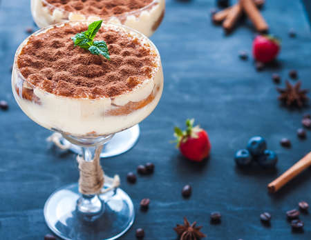 luxury tiramisu dessert in a cocktail glass decorated with cocoa on the wooden background Reklamní fotografie