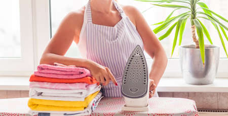 Young beautiful woman ironing clothes.