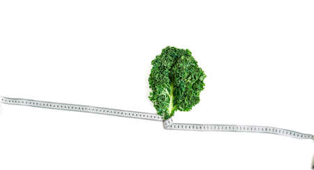 kale wrapped in measuring tape, concept diet, slimming, healthy eating top view Reklamní fotografie
