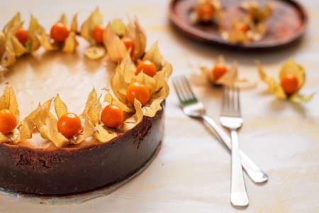 Freshly baked, whole New York cheesecake garnished with physalis
