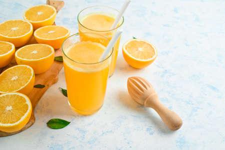 fresh orange Juice and oranges on the cutting board