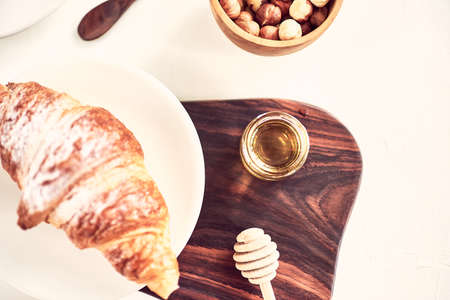 Coffee and croissant on wooden table. French breakfast. Top view flat lay with copy space for your text
