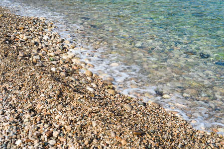 pebble beach background of transparent sea water and bottom, with stones and waves