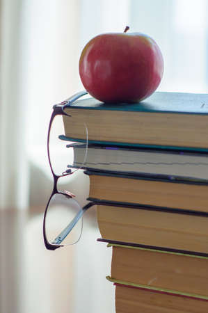 Glasses and apple on a pile of books. Banco de Imagens