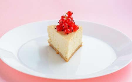 Slice of Plain New York Cheesecake on white plate on wooden background Banco de Imagens