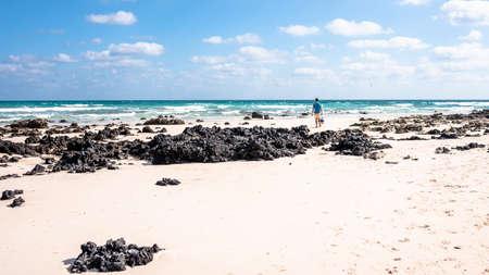 freedom concept, a man walks along the beach on the island of Fuerteventura Spain Banco de Imagens