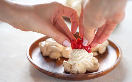 the process of creating Pavlova dessert, decorating the meringue with cream from the culinary bag Banco de Imagens