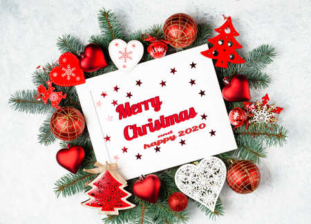 Christmas photoframe surrounded by branches of a New Year tree, red Christmas decorations. Top view, flat lay. Merry christmas and happy 2019 text