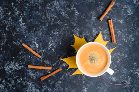 Autumn coffee composition, coffee cup with foam, cinnamon, autumn leaf at black background. Fall hot drinks, cafe and bar concept Standard-Bild