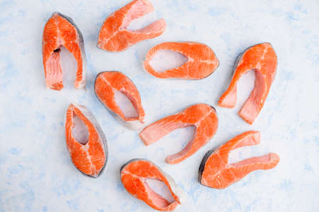 raw salmon steaks pattern on a blue background top view