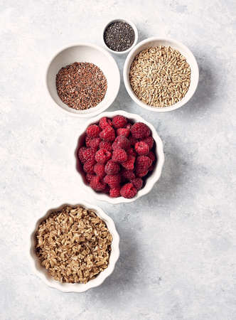 oatmeal with raspberries chia seeds and honey on a white table