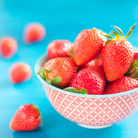 ripe strawberries in a bowl on a colorful background