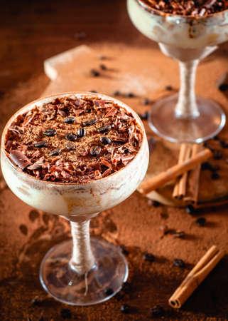 italian dessert tiramisu in an elegant cocktail glass, the concept of sweet life, luxury