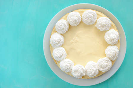classic cheesecake on a white plate, decorated with cream