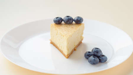 Slice of Plain New York Cheesecake on white plate on wooden background Standard-Bild