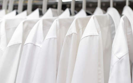 white mens shirts hang on the shoulders in the closet