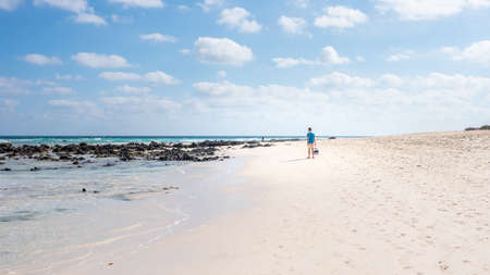 freedom concept, a man walks along the beach on the island of Fuerteventura Spain, Corralejo beach