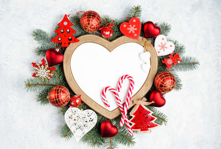 Christmas frame in the shape of a heart is surrounded by branches of a New Year tree Christmas decorations with copy space. Top view, flat lay. Nature New Year concept.