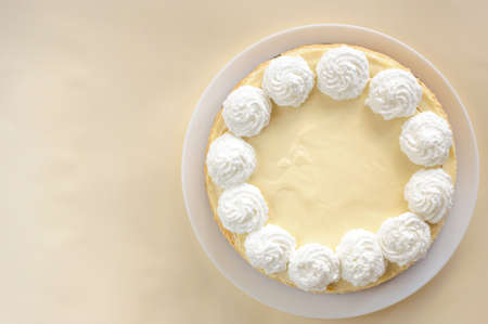 classic cheesecake on a white plate, decorated with cream, top view