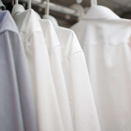 white mens shirts on hangers in wardrobe