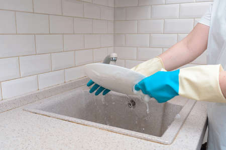 female hands in blue gloves wash a plate in a white kitchen