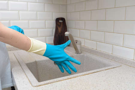 Woman washes dishes. Washing dishes - hands with gloves in kitchen, housework