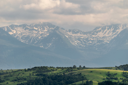 foreground: Snow capped mountains with hills in the foreground, Retezat, Romania Stock Photo