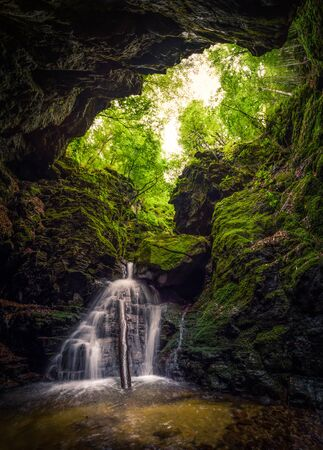 Waterfall and rocks covered with moss in a forest cave Reklamní fotografie