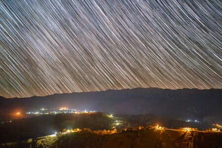 Star trails over the Pestera village in Piatra Craiului mountains from Romania