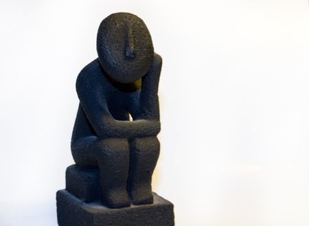 a coal statue of a man sitting and thinking with hand touching his face