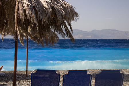 empty seats and umbrellas on a resort at a greek beach with waves and winds of autumn Stock Photo
