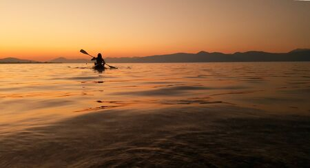 man rowing and a conoe at the calm water a summer evening in the ocean at greece