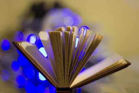 turning the page: open book pages flip change and bokeh lights on the background