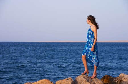 mujer mirando el horizonte: La ni�a en un vestido azul, de pie sobre una piedra y con vista al mar