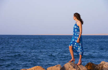 The girl in a blue dress standing on a stone and looking at the sea