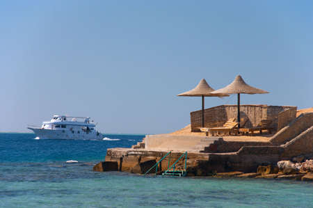 The ship passing by a beach with umbrellas and chaise lounges Stock Photo - 1157081