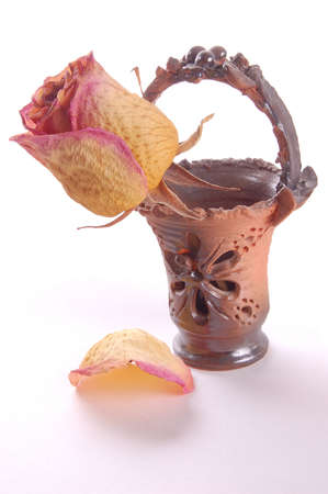 sapless: dry rosebud in the decorated vase and one petal at the bottom whith shadow on white
