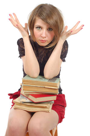 the girl sit in panic with heap of books photo