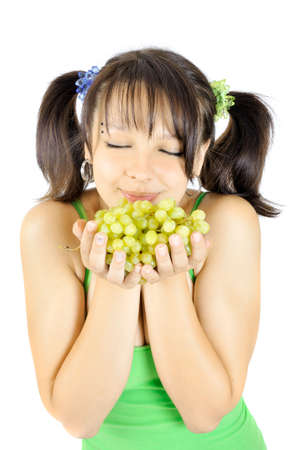 foretaste: Nice young girl smells grapes, isolated on white